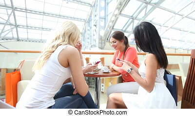 Women in cafe after shopping - Happy women with smartphones...