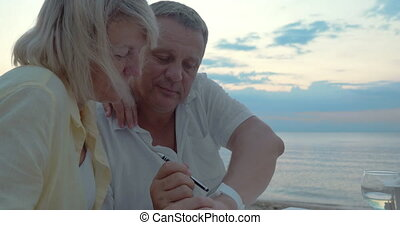 Man and woman using smart watch outdoor - Senior couple...