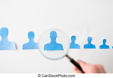 close up of paper human shapes on white board - business,...