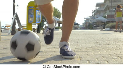 Man dribbling a football outdoor - Steadicam close-up shot...