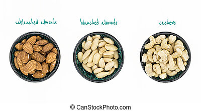 Unblanched almonds, blanched almonds and cashews in bowls,...