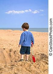 Digging a hole. - Toddler on the beach admiring a huge hole...