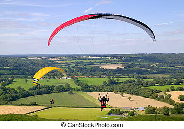 Paragliders - Two paragliders flying across a rural scene.