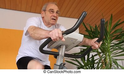 exercise machine - senior cycling on an exercise machine