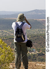 Explorer with binoculars - View of a nature explorer looking...