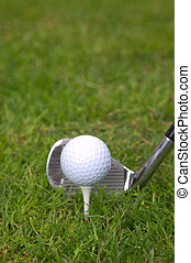 Iron tee shot - Golf ball on a tee with an iron club behind