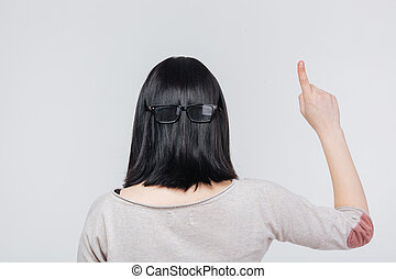 Back view portrait of a brunete girl pointing finger up...