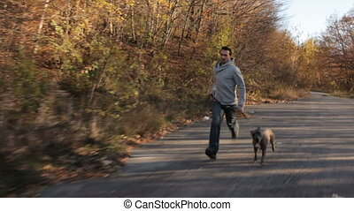 Man With Dog Jogging In Autumn Park - Young man in warm...