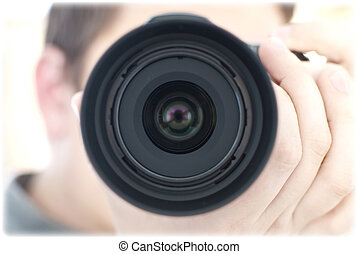 Lens and photograph - Croped lens closeup, blured hands of...