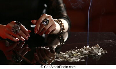 Witch - fortune teller reading fortune close up smoking ash...