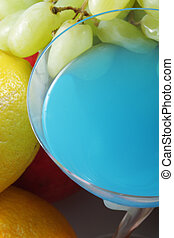 Blue cocktail in glass among fruits closeup photo above view
