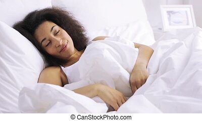 african woman sleeping in bed at home bedroom - rest,...