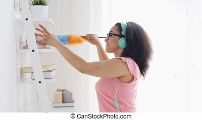 happy african woman with duster cleaning at home - people,...