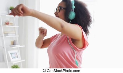 happy african woman in headphones dancing at home - people,...
