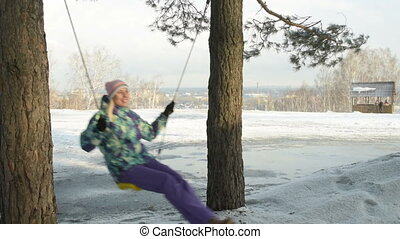 Girl going on the swings outside the town in winter - Happy...