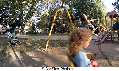Children Girl and boy on a swing ride . - Two cute children...