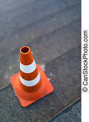 traffic cone, with white and orange stripes on gray...