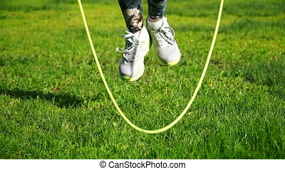 footage woman jumping on a skipping rope in a park close-up....