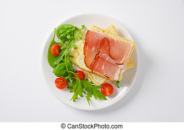 bread with ham and salad greens - slices of white bread with...