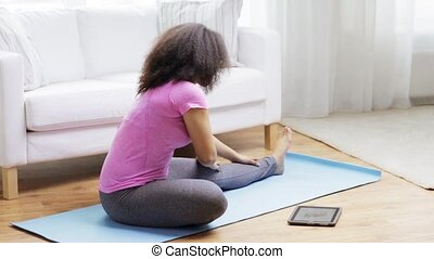 african woman with tablet pc exercising at home - fitness,...