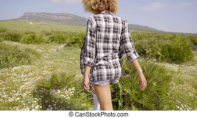 Young woman walking away through open countryside