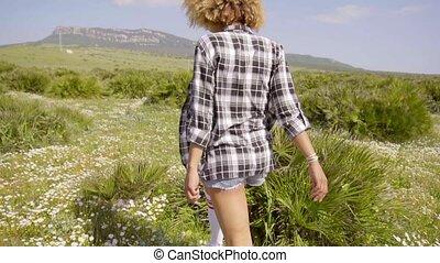 Young woman walking away through open countryside