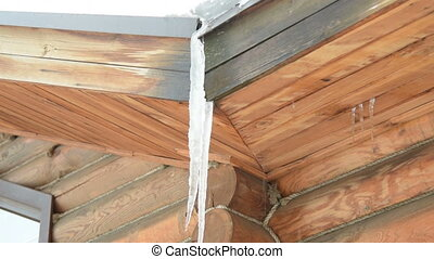 Melting icicle on wooden house - Melting icicle and water...