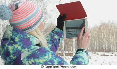 Girl with pad making photos of winter wood