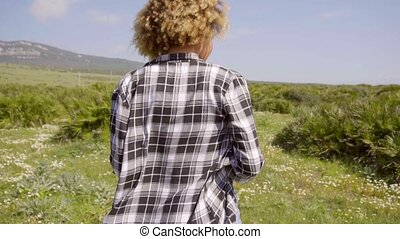 Young woman walking through a country meadow - Young woman...