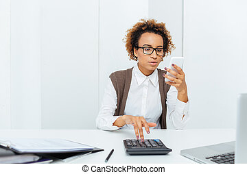 Thoughtful african woman accountant working with calculator...