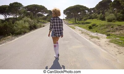 Girl Walking Down The Country Road - Rear view of young...