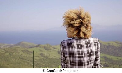 Young woman sitting admiring the coastal view of mountains...