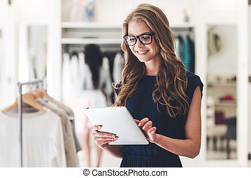 Starting new business. Beautiful young woman using digital tablet with smile while standing at the clothing store