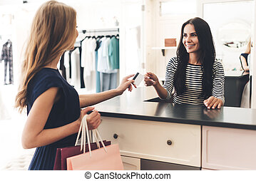 Can I pay with my card Beautiful young woman with shopping...