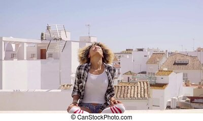 Woman Meditating On Rooftop - Young happy mixed-race woman...