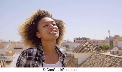 Young Woman on Urban Rooftop on Windy Sunny Day - Head and...