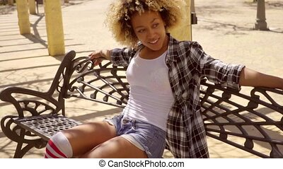 Attractive young woman relaxing on a park bench - Attractive...