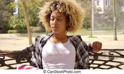Young Woman Relaxing on Park Bench on Sunny Day - Waist Up...