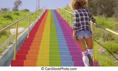 Young woman walking up a colorful flight of steps outdoors...