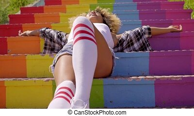 Model Lying On Colorful Stairs - Young mixed-race woman...