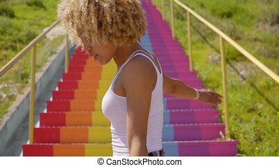 Sexy young woman dancing on rainbow colored steps - Sexy...