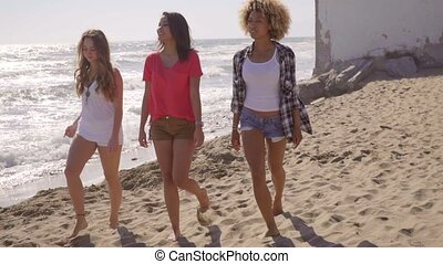 Three attractive young women walking on a beach - Three...