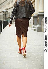 Woman wearing elegant skirt and red high heel shoes in old...