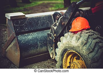 Construction Safety Helmet on Bulldozer Tire. Heavy...
