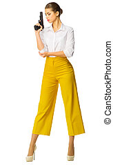 Young woman in yellow with gun