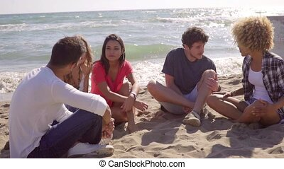 Group of diverse young friends chatting on a beach - Group...