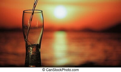 Mineral water is being poured on the sunset background - A...
