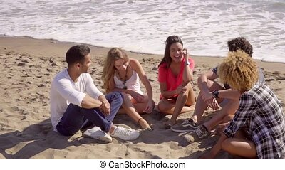 Young People Sitting On The Beach - Group of five mixed-race...