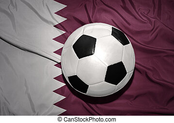 black and white football ball on the national flag of qatar...