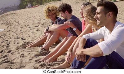 Group of multiracial people sitting on a beach - Group of...